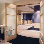 PHARMACIA : portes et cadres, panneaux muraux (lambris) et comptoir de réception en érable