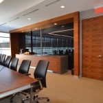 AGROPUR CAMPUS : walnut credenza, black glass sliding door, walnut trims and doors